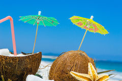 Cocktail umbrellas in coconuts halves Stock Photography