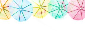 Cocktail umbrellas isolated on white background. Closeup festive bright colorful frames of cocktail umbrellas; tropical colors with space for copy text stock photo