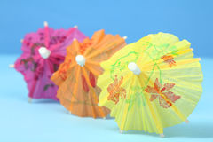 Cocktail umbrellas. Multi-colored cocktail umbrellas on a blue background royalty free stock images