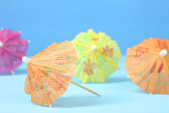 Cocktail umbrellas. Multi-colored cocktail umbrellas on a blue background royalty free stock photography