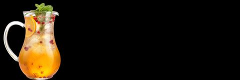 Cocktail in una caraffa di vetro con l'arancia e bacche e sciroppo dolce Bibita isolata su un fondo nero bandiera immagine stock libera da diritti