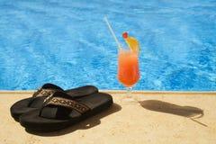 Cocktail und Hefterzufuhren stehen auf Rand des Pools. Lizenzfreies Stockfoto