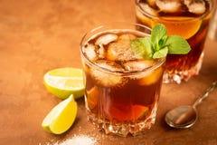 Cocktail van rum en kolaijsblokjes en kalk in een glasdrinkbeker op een donkere bruine achtergrond Sterke alcoholische drank royalty-vrije stock fotografie