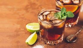 Cocktail van rum en kolaijsblokjes en kalk in een glasdrinkbeker op een donkere bruine achtergrond Sterke alcoholische drank royalty-vrije stock foto