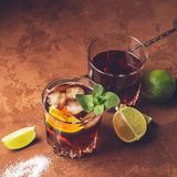 Cocktail van rum en kolaijsblokjes en kalk in glasdrinkbekers op een donkere bruine achtergrond Sterke alcoholische drank stock afbeelding