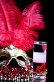 Cocktail and Venetian mask. Multi-Layered cocktail and Venetian mask on a black background Stock Photo