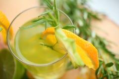 Cocktail verde que está na madeira, decorada com laranja, carambola, cal e alecrins Apronte para party Vista superior Imagens de Stock Royalty Free