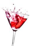 Cocktail vermelho com espirro no vidro inclinado foto de stock