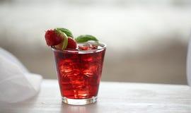Cocktail vermelho com o gelo, decorado com folha da hortelã, cal e trawberry no fundo claro Fotos de Stock Royalty Free