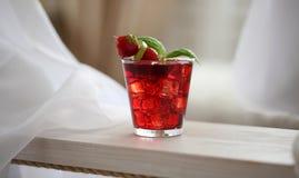 Cocktail vermelho com o gelo, decorado com folha da hortelã, cal e trawberry no fundo claro Fotografia de Stock