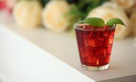 Cocktail vermelho com o gelo, decorado com a folha da hortelã no fundo claro Imagem de Stock Royalty Free