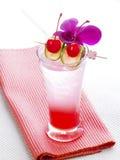 Cocktail vermelho tailandês com orquídea, cal e cereja Fotos de Stock Royalty Free