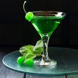 Cocktail vert avec la cerise de marasquin dans un verre de martini Photographie stock libre de droits