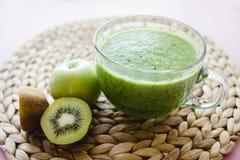 Cocktail vert sain dans une tasse en verre avec les ?pinards, le kiwi et l'Apple vert images stock
