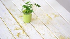 Cocktail vert sain de fruit et de vegan avec le brin du persil sur la table en bois blanche avec le sable banque de vidéos