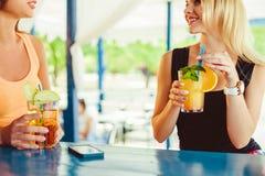 Cocktail in vrouwenhand op het open terras in bar tijdens de zomertijd stock foto
