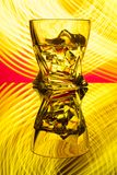 Cocktail whiskey a glass with pieces ice of party reflection a concept of hourglasses yellow light effects on red. Background Royalty Free Stock Photos