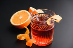 Cocktail with whiskey, rum, and oranges in the background. Black background. Stock Photography