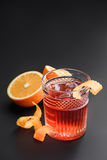 Cocktail with whiskey, rum, and oranges in the background. Black background. Royalty Free Stock Images