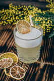 Cocktail Whiskey Sour. On a wooden board with dried fried oranges and mint Royalty Free Stock Photo