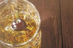 Cocktail from whisky with cherry in two glasses on a wooden back. Cocktail from whisky with cherry on a wooden background. Copy space. Food background. Toned Royalty Free Stock Photo
