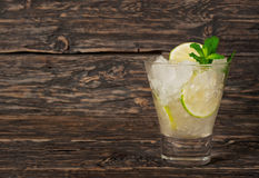 Cocktail with white rum or gin with ice, lime, mint. Cocktail with white rum or gin with ice, lime and mint on a dark wooden background with copy space. Summer Stock Photo