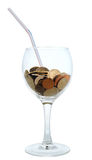 Cocktail: wineglass with the heap of coins. And straw Royalty Free Stock Photography
