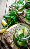 Cocktail on a wooden stand with limes and mint. Stock Photos