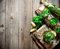 Cocktail on a wooden stand with limes and mint. Free space for text . Stock Photography