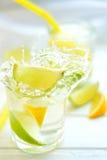 Cocktailcitroen en kalk in een glas met waterplonsen Stock Afbeeldingen
