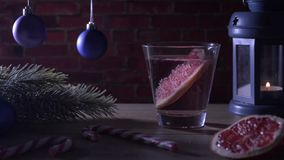 Cocktailgrapefruit, kaars, spartak met Kerstmisspeelgoed en suikergoedriet stock video