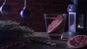 Cocktailgrapefruit, kaars, spartak met Kerstmisspeelgoed en suikergoedriet stock footage
