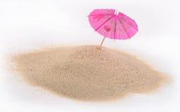 Cocktailparaplu in zand op een wit royalty-vrije stock afbeeldingen