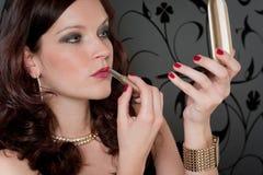 Cocktailparty-Frauen-Abendkleid wenden Lippenstift an Lizenzfreie Stockfotos