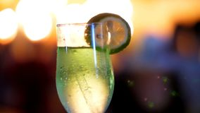 Cocktailparty, Getränk mit Eis, in einem Glas mit einem Stroh und mit einer Scheibe der Zitrone, in den Strahlen von Laibungen ve stock footage