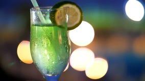 Cocktailparty, Getränk mit Eis, in einem Glas mit einem Stroh und mit einer Scheibe der Zitrone, in den Strahlen von Laibungen ve stock video footage
