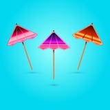 Cocktailregenschirme auf einem blauen Hintergrund mit Schatten Lizenzfreie Stockfotos