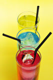 Cocktails. Some glasses with cocktails of different colors on a yellow background Royalty Free Stock Images