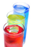Cocktails. Some glasses with cocktails of different colors on a yellow background Stock Photo