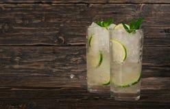 Cocktails avec le rhum ou le genièvre blanc avec de la glace, chaux, menthe Images libres de droits