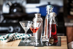 Cocktails on Bar Counter. Cocktails and supplies on a bar counter in front of a stove Stock Image
