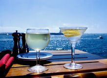 Cocktails on the Bay. A Glass of wine, a martini, the sun and brilliant blue water Stock Photo
