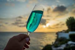 Cocktails bleus aux vues du Curaçao de coucher du soleil Photographie stock libre de droits