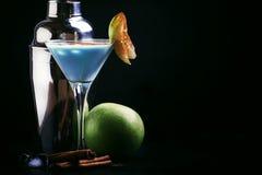 Cocktails bleus avec la liqueur, la crème et la pomme verte, outils de barre sur un fond noir de compteur de barre, l'espace de c image libre de droits