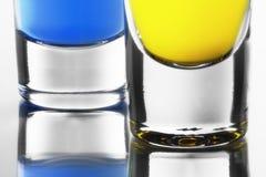 Cocktails bleus et jaunes dans des verres à liqueur propres Photographie stock libre de droits