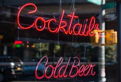 Cocktails and cold beer neon sign. In the window of a bar stock photography