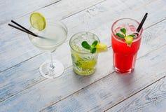 Cocktails colorés Mojito, cocktail rouge avec de la glace et la chaux, margarita sur la fin en bois de table  Photographie stock libre de droits