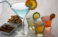Cocktails. Colorful alcoholic cocktails with olives and peanuts snacks Stock Photo