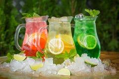 Cocktails d'été dans des cruches dans la glace avec la chaux et la menthe, sangria Images stock