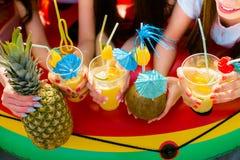 Cocktails d'agrume d'été avec des parapluies dans les mains des filles Re Images stock
